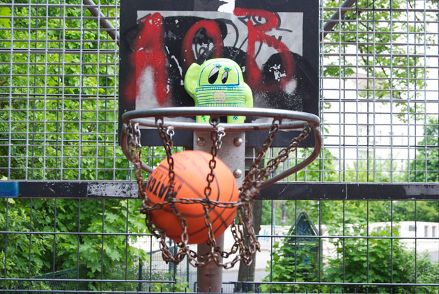 astro naut street art toy in a basketball hoop