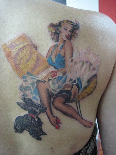 this nice pinup girl tattooed on the back of this guy's shoulder blade.