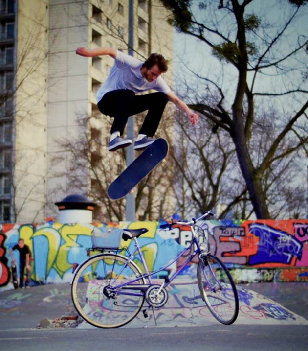 skateboarder kick flip over a bike